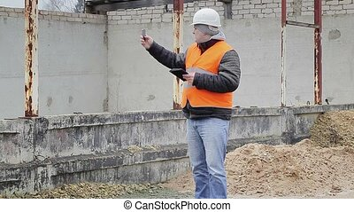 Civil engineer talking on cell phone near unfinished...