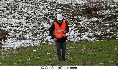 Civil engineer walking up to hill and using tablet PC