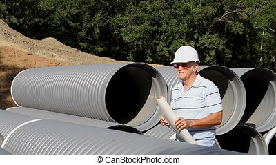 Civil Engineer With Prints - Civil engineer stands by a...