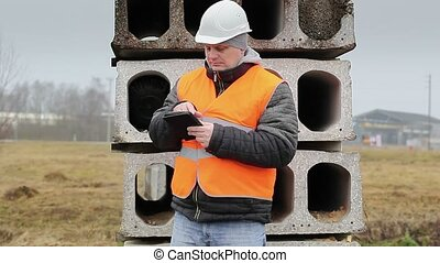 Civil engineer with tablet PC in construction panels