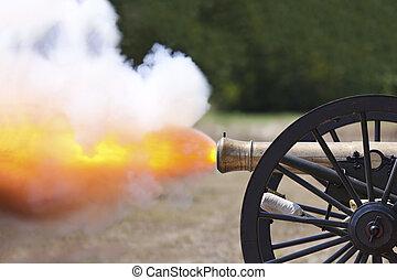 A close up shot of a Civil War cannon fireing at a civil war re-enactment.