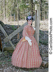 outdoor color portrait of an attractive young girl in a Civil War era 1860s dress