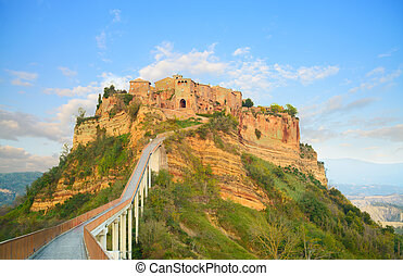 Civita di Bagnoregio landmark, bridge view on sunset. Italy