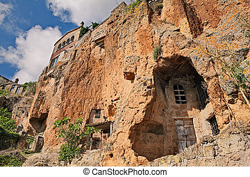 Civita di Bagnoregio, Viterbo, Lazio, Italy: the rock face of the tuff hill with caves and rock-cut cellars