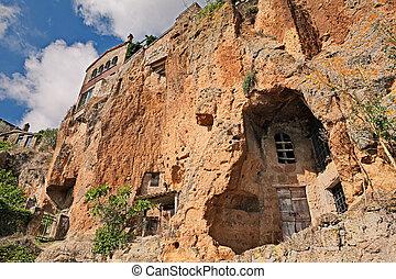 Civita di Bagnoregio, Viterbo, Lazio, Italy: the rock face of the tuff hill with caves and rock-cut cellars
