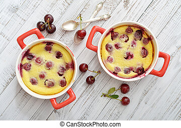 Clafoutis with cherries in red ramekin on wooden background
