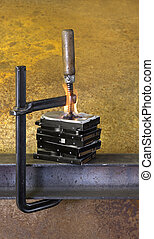 clamp pressing on stack of burning hard drives