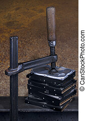 clamp pressing on stack of hard drives