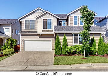 Clapboard sidinig house. Garage with driveway and curb...