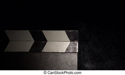 Clapboard with a cloud of chalk dust. Close up. Black...