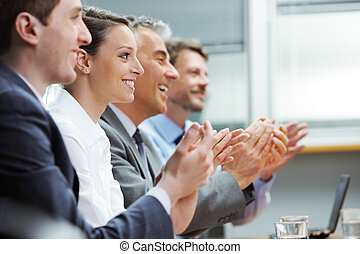 Clapping business people