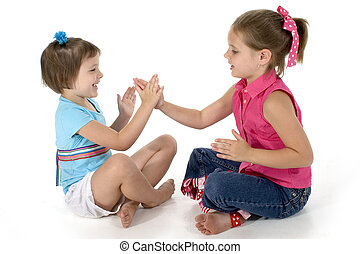 Two sisters, 4 and 6, playing clapping games.