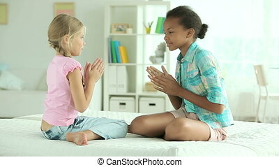 Clapping hands - Cheerful girls sitting on the bed and...