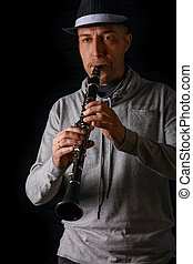 clarinet in the hands of a man on a black background