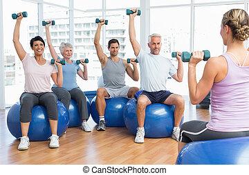 clase salud, con, dumbbells, sentado, en, pelotas de ejercicio