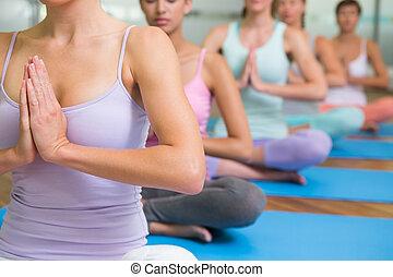 clase yoga, en, postura lotus, en, condición física, estudio
