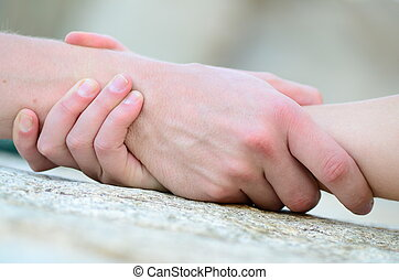 clasped hand for help on a granit rock