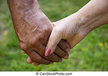 clasped hands of adults, seniors, golden age