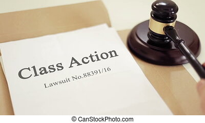 Class action folder with gavel placed on desk of judge in court