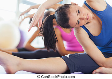 Class and instructor doing stretching pilate exercises in...