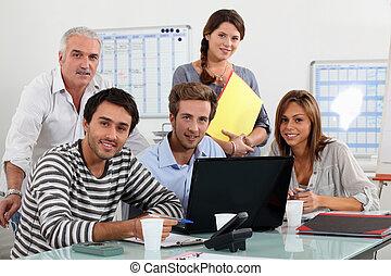 Class and teacher gathered around laptop - Class and teacher...