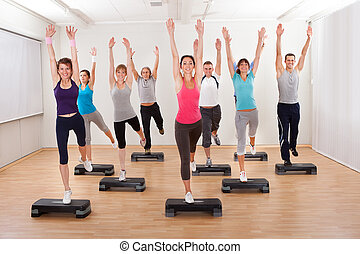 Class doing aerobics balancing on boards - Diverse group of...