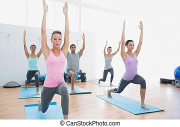 Class doing pilate exercises in fitness studio - Sporty...