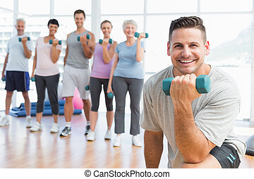 Class exercising with dumbbells in