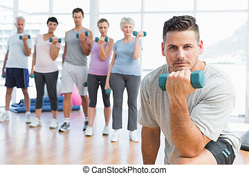 Class exercising with dumbbells in gym