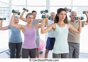Class exercising with dumbbells in gym - Fitness class...