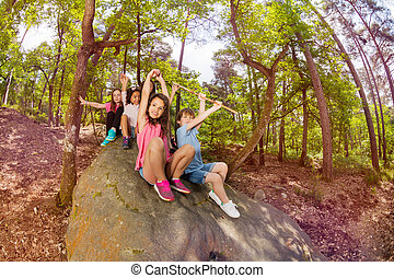 Class group of kids sit on the rock in forest