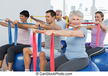 Class holding out exercise belts while sitting on fitness...