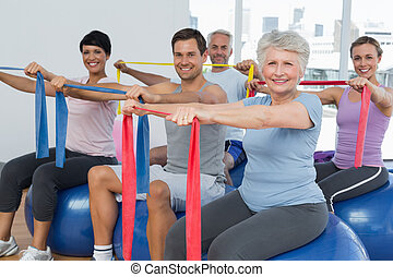 Class holding out exercise belts while sitting on fitness balls