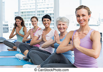 Class sitting with joined hands in row at yoga class -...
