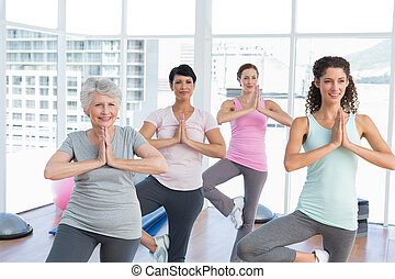 Class standing in namaste pose at yoga class - Female...