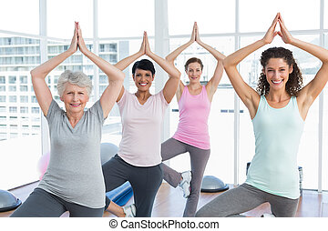 Class standing in tree pose at yoga class - Portrait of a ...