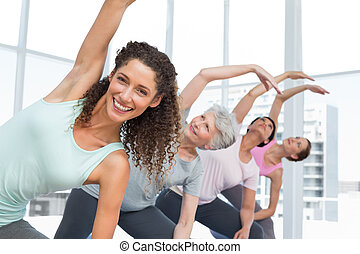 Class stretching hands at yoga class