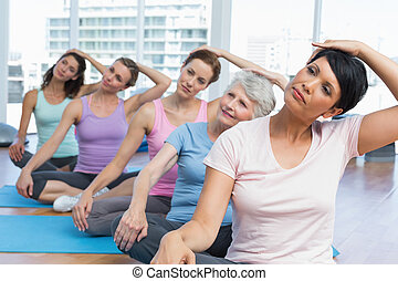 Class stretching neck in row at yoga class - Female trainer...