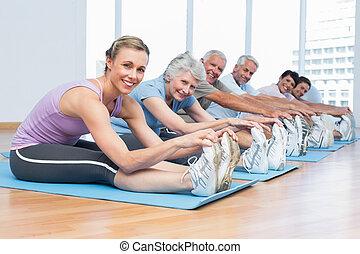classe, esticar, mãos, para, pernas, em, classe ioga