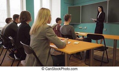 classe, femme, étudiants, conversation, pendant, leçon, prof