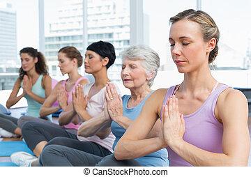 classe, sentando, com, mãos juntadas, uma fileira, em, classe ioga