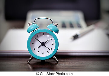 classic alarm clock standing on business table