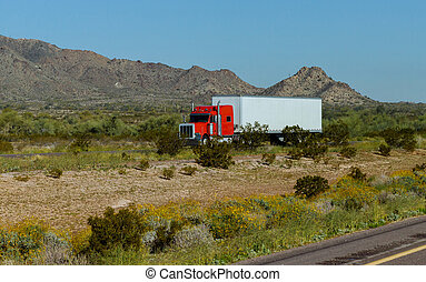 Classic American big rig semi truck with transporting on flat bed semi trailer driving on the road along mountain rock