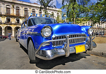 Blue classic american car in havana street with eroded buildings in the background, cuba