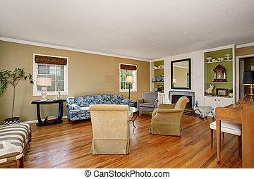 Classic American living room interior. Beige and green walls, hardwood floor and blue sofa.