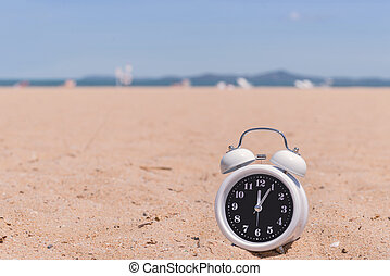 Classic analog clocks in sand on the beach