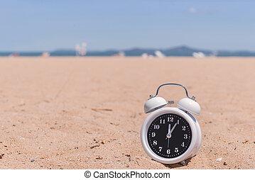 Classic analog clocks in sand on the beach