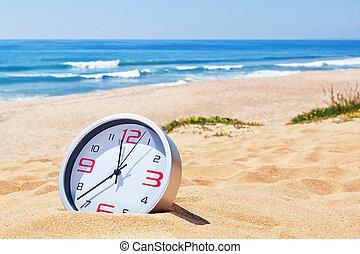 Classic analog clocks in the sand on the beach near the sea....