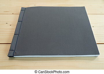 classic black notebook on the wood table.