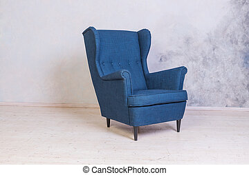 Classic blue chair. loft interior. Comfortable armchair against concrete wall background. Scandinavian style. Minimal Modern Furniture Recliner Object in Elegance Interior. Living Room Fashion Design with Copy Space
